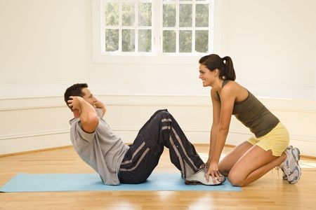situp: Woman holding mans feet down as he does sit up exercises.