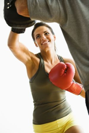 Woman wearing boxing gloves hitting training mits man is holding.