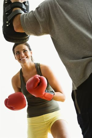 male boxer: Woman wearing boxing gloves hitting training mits man is holding.