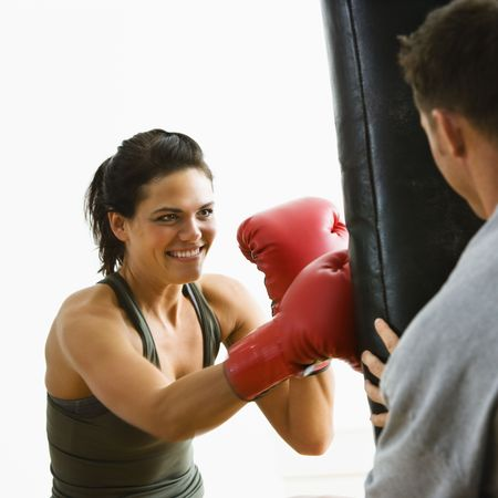 Woman wearing boxing gloves hitting training mits man is holding. photo