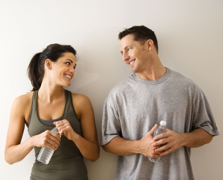 eachother: Man and woman at gym in  attire holding water bottles standing against wall smiling at eachother.
