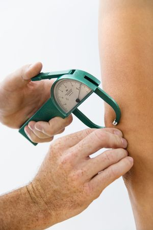 measuring: Close-up of adult male hand using caliper to test body fat. Stock Photo