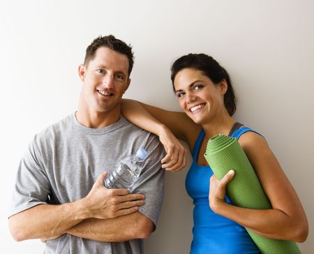two people talking: Man and woman at gym in  attire holding water bottles and yoga mat standing against wall smiling. Stock Photo