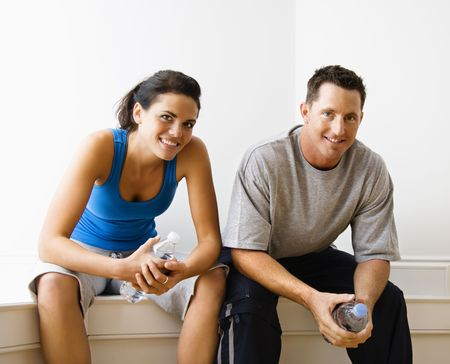 Portrait of young adult woman and man sitting wearing active wear. photo