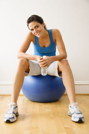 Woman holding water bottle sitting on balance ball at gym smiling. Stock Photo - 2615630