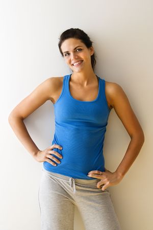 Portrait of woman in fitness attire smiling with hands on hips. photo