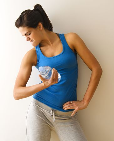 Portrait of woman in fitness attire flexing arm muscle holding water bottle. Stock Photo - 2615849