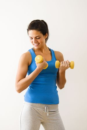 Woman lifting hand weights and smiling. photo