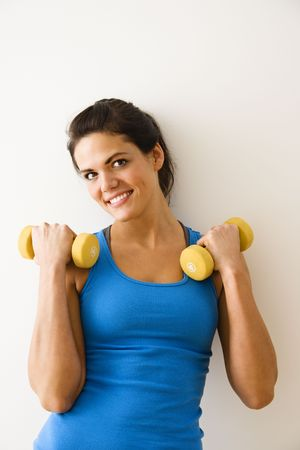 Woman holding hand weights and smiling. photo