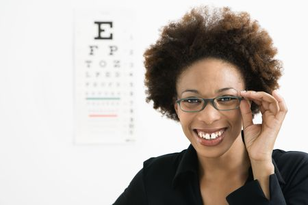 Woman wearing eyeglasses with medical eyechart in background. photo