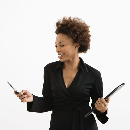 sms: Businesswoman looking at cellphone smiling against white background.