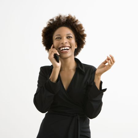 Woman talking on cellphone smiling against white background. photo