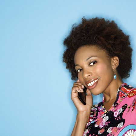 Woman with afro wearing vintage print fabric smiling holding cellphone. photo