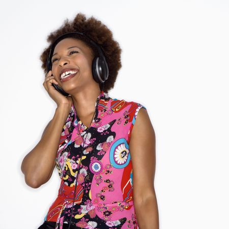Woman with afro wearing vintage print fabric and listening to headphones smiling. photo