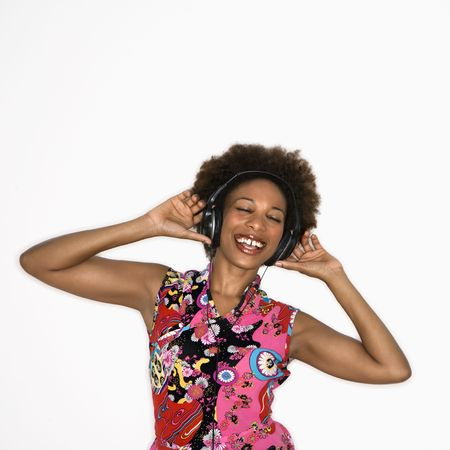 Woman with afro wearing vintage print fabric and listening to headphones smiling and dancing. photo