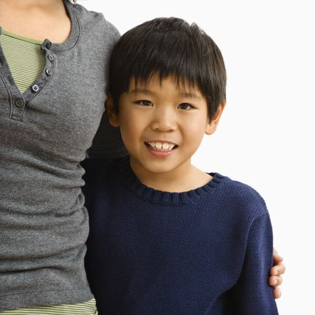 Boy standing smiling with mother standing next to him with arm around him. Stock Photo - 2616076