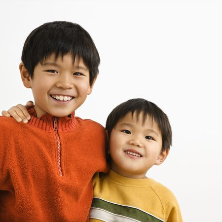 Portrait of young Asian brothers with arms around eachother smiling. photo