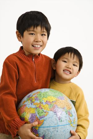Two Asian boys holding world globe and smiling. Stock Photo - 2616052
