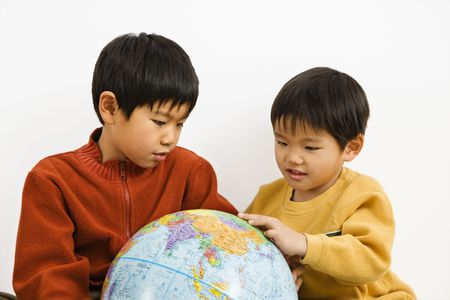Two Asian boys looking and pointing at world globe photo
