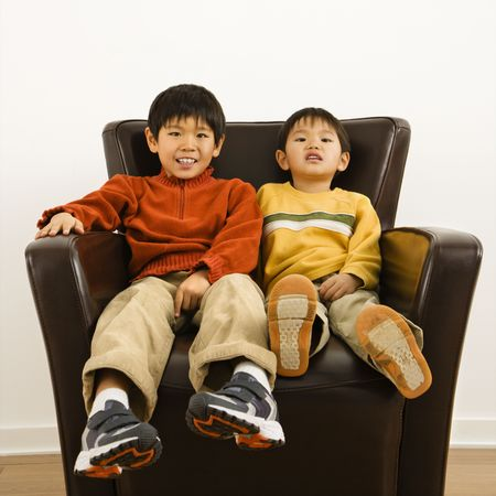 Two Asian brothers sitting in chair smiling. Stock Photo - 2615827