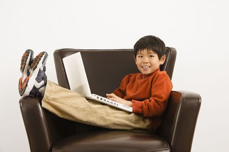 Asian boy with laptop computer sitting in chair smiling. Stock Photo - 2615777