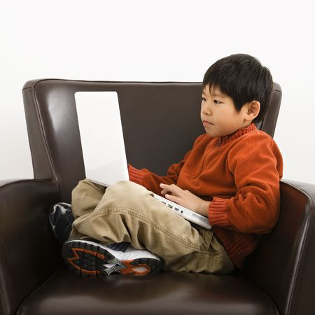Asian boy with laptop computer sitting in chair. Stock Photo - 2615845