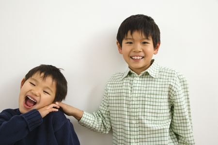 Two young Asian brothers playing and laughing. Stock Photo - 2615999
