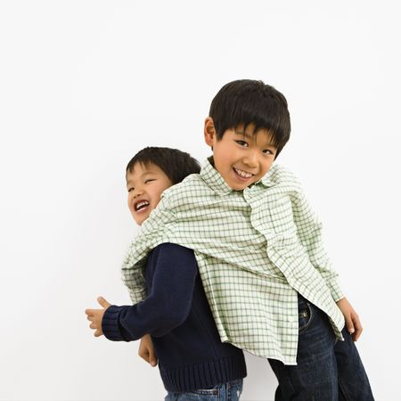 Two young Asian brothers playing and laughing. photo