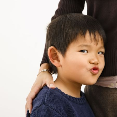 Young Asian boy making funny face standing next to mother. Stock Photo - 2622851