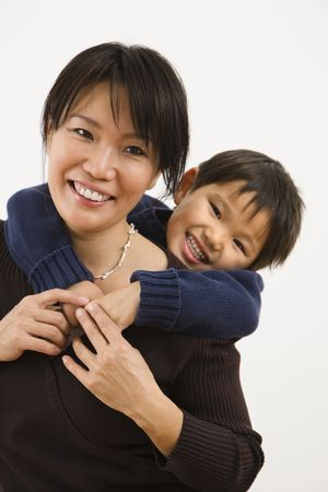 Asian mother with young son hugging her from behind smiling.