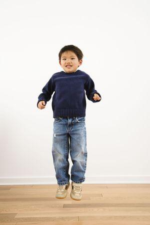 persona saltando: J�venes de Asia muchacho saltar en el aire hasta sonriente.  Foto de archivo