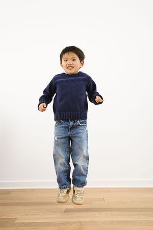 Young Asian boy jumping up into air smiling. Stock Photo