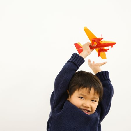 indoors: Young Asian boy playing with plastic toy airplane.