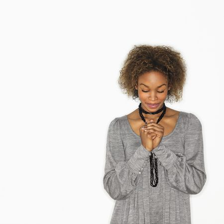 Woman with hands clasped together in prayer and eyes closed.