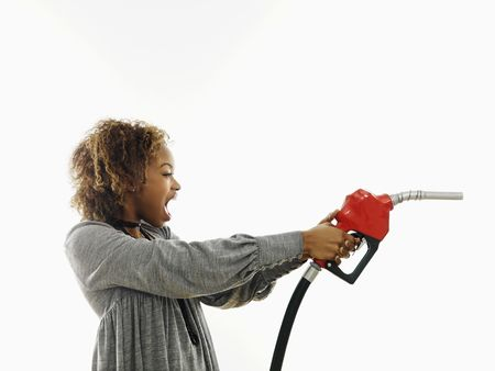 Portrait of pretty young woman holding gas pump nozzle like a gun making angry facial expression on white background. photo