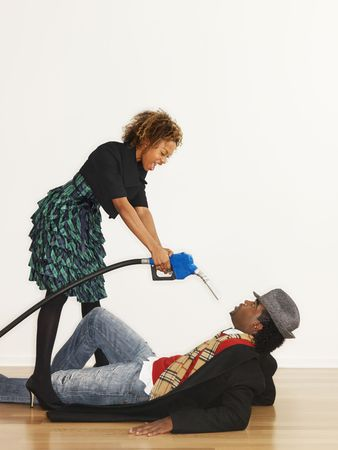 accuse: Man on floor with angry woman standing over him pointing gasoline pump nozzle at him like a gun. Stock Photo