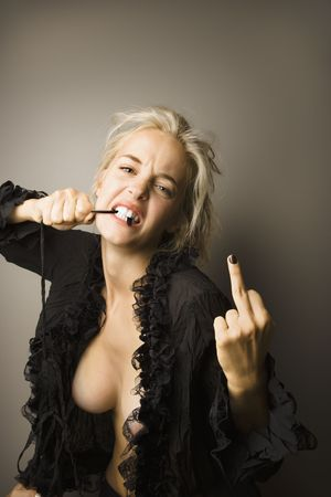 one finger: Caucasian  woman biting on string and showing middle finger to viewer.