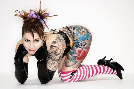 dreadlock: Adult caucasian woman with tattoos leaning on floor.