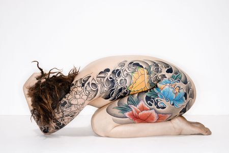 Nude caucasian woman with tattoos sitting on floor. photo