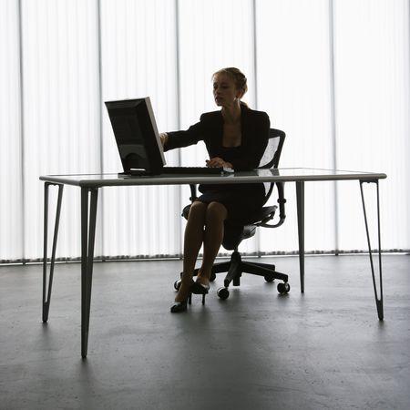 backlit: Silhouet van blanke zakenvrouw zittend aan een bureau met een computer werkt.