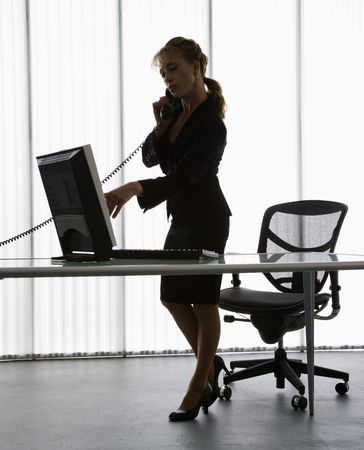 telephone: Silhouette of Caucasian businesswoman standing at computer  desk on telephone. Stock Photo