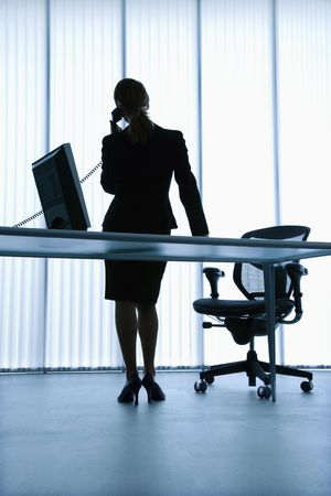 Silhouette of Caucasian businesswoman standing at computer desk on telephone. photo