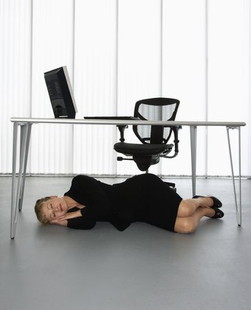 sleeping at desk: Caucasian businesswoman sleeping on floor under computer desk. Stock Photo