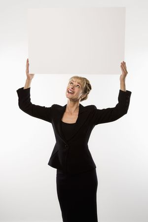 business sign: Caucasian businesswoman standing holding blank sign above head.