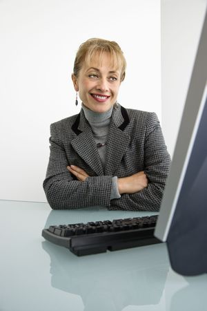 Caucasian woman looking at computer and smiling with arms crossed. Stock Photo - 2655352