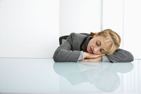 Caucasian woman sleeping on desk with head on hands. photo