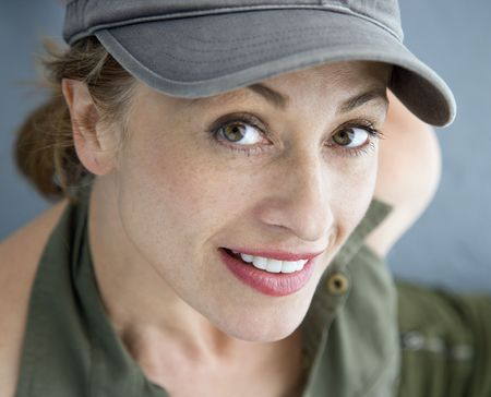 Caucasian woman wearing hat smiling at viewer. photo