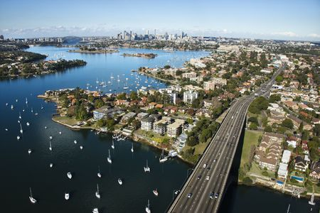 aerial photograph: Aerial view of Victoria Road bridge and boats with distant downtown skyline in Sydney, Australia.