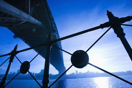 port jackson: Low angle view at dusk from under Sydney Harbour Bridge in Australia with view of skyline and harbor. Stock Photo