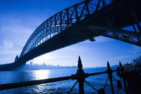 port jackson: Low angle view of Sydney Harbour Bridge at dusk with harbour and distant Sydney skyline, Australia. Stock Photo